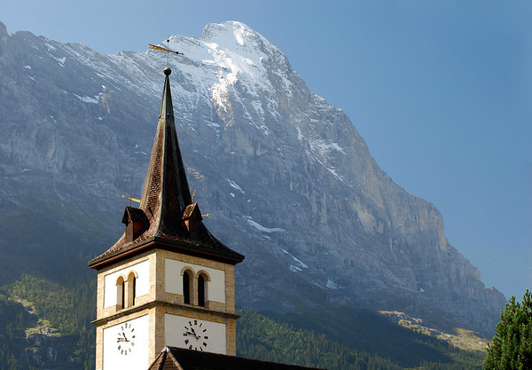 Beyond the clock tower and steeple of the Dorpkirche (village church) in Grindelwald - up to northwest face to the snow-capped summit of the Eiger - canton of Bern