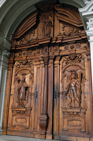 Wooden pillar trumeau between the wood carved double doors, depicting a bishop and soldier, symbolizing the close relation between spiritual and wordly powers at the time when the Hof Church was built, back in 1644 - Lucerne
