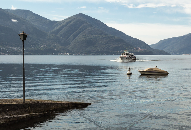 Ferry arriving in Ascona on placid Lake Lugano surrounded by mountains, Switzerland