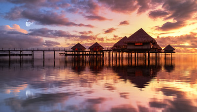 Tahiti bungalows with reflection in water during sunset