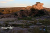 Nearing sunset with the day's last rays upon Eagles Beak - a 50 ft (15 m) tall outcrop of igneous granite rock protruding from a river island - with the shadowed Llano River foreground amongst the riparian vegetation - and distal the live oaks and junipers along the slope of Long Mountain - eastern Llano county.