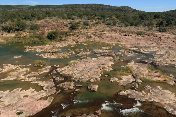 Llano River - displaying its pink intrusive igneous granite rock riverbed,  amongst the riparian vegetation - from here atop Eagles Beak - beyond to the slope and ridge along Long Mountain.