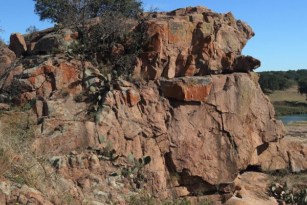 Eagles Beak - a intrusive igneous pink granite rock outcrop standing about 50 ft (15 m) above the Llano River below - here amongst the lithophytic lichens, live oaks, prickly-pear cacti, and tussock grass upon the river island.