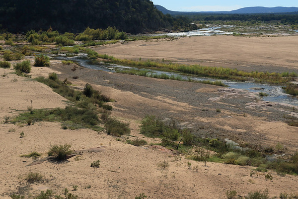 From atop Eagles Beak - viewing at the southwestern and southern end of the river island - amongst the riparian vegetation, sand/pebble bar, granite riverbed along the Llano River, and the mostly shadowed and steep limestone rock outcrop slope - distal to the Riley Mountains, with the northern edge of Packsaddle Mountain (l).
