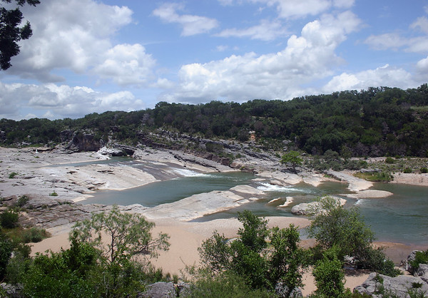 Pedernales Falls - during the late spring season - sourced by the approximate 100 mi. (160 m) long Pedernales River, with its headwater originating in Kimbel county and terminating into Lake Travis, along the Colorado River, in Travis county.