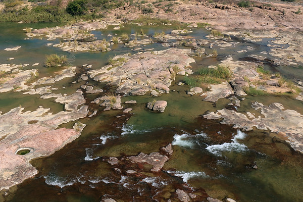 From atop Eagles Beak - down to the flowing Llano River - displaying its pink intrusive igneous granite rock riverbed amongst the reeds, sedges, and tussock grass vegetation.