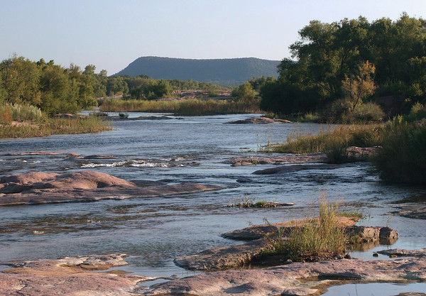 Late-afternoon sunlight and shadows among the riparian vegetation and granite rock along the Llano River - with beyond to Packsaddle Mountain - eastern Llano county - Hill Country of Texas.