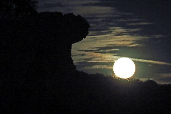 Blue Moon rising beyond the granite rock silhouette of Eagles Beak - amongst the clouds on Halloween - eastern Llano county.