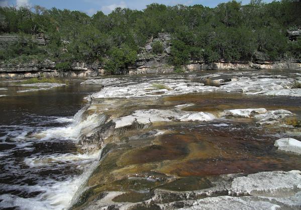 Waterfall along Flat Rock Creek - amongst the sedimentary limestone rock and vegetation of the Edwards Plateau ecoregion - during the late summer season.