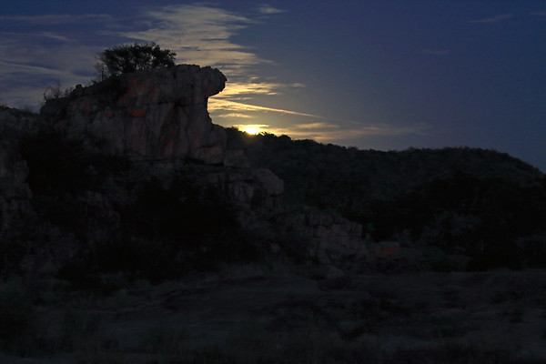 Blue Moon rising above the distal ridge of Long Island - with foreground the igneous granite rock outcrop of Eagles Beak - eastern Llano county.
