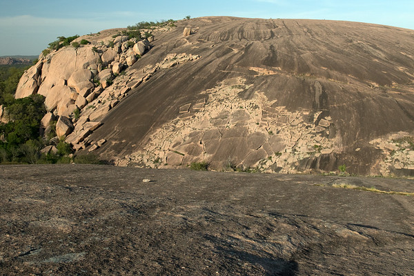 The mystically magical megalithic monument of - Enchanted Rock State Natural Area (1978) - National Natural Landmark (about 20 in TX) - this intrusive igneous granite batholith (or pluton), or monadnock (Native American) has a prominence of about 425 ft. (130 m), elevation of around 1,825 ft. (556 m), with an exposed surface area of around 1 mi² (2.6 km²), yet this solid rock covers about 62 mi² (160 km²), most of which is still still below the surface - this image viewing from atop Little Rock, during the early spring season, near sunset, to the western slope of Enchanted Rock - southwestern Llano county.