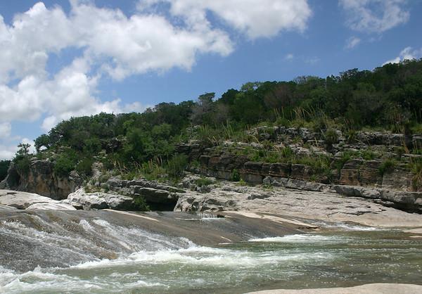 Pedernales Falls - Pedernales River - sedimentary limestone rock - sotol agave bloom stalks, yuccas, live oaks, and junipers - cumulus clouds.