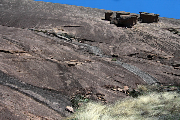 Exfoliated and eroded granite rock boulders along the southwestern slope of Little Rock - with the tussock/prairie grass below.