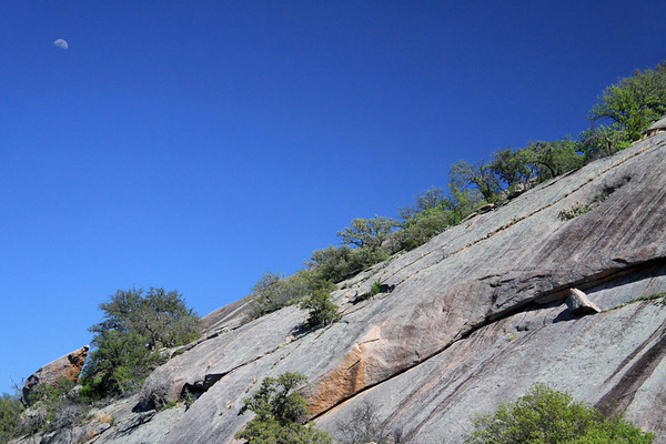 1st Quarter Moon (waxing - or becoming more visible night by night) - above the intrusive igneous granite rock slope of Enchanted Rock - during the mid-afternoon sunlight, under a naked early spring season sky.