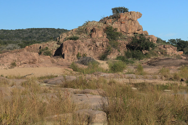 Eagles Peak - its western view of the  50 ft (15 m) pink granite outcrop upon the river  island - with a glimpse of the Llano River foreground and distal the slope and ridge along Long Mountain - eastern Llano county.