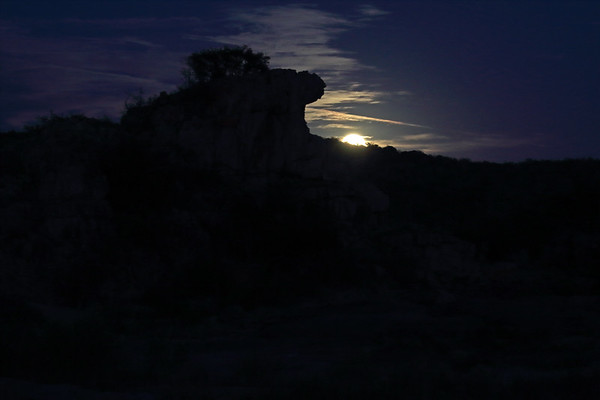 Blue Moon rising above the ridge of Long Mountain - with foreground the granite rock silhouette of Eagles Beak - eastern Llano county.
