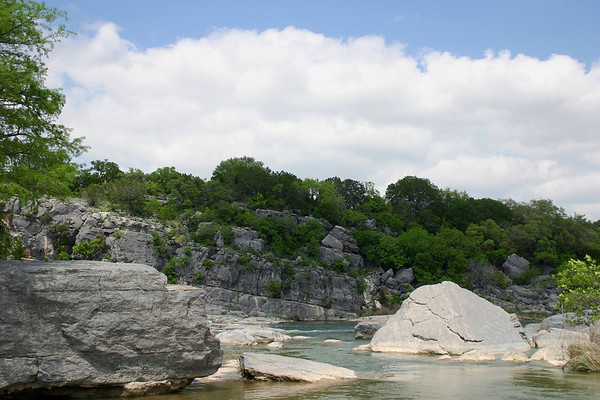 Sunlight and shadows upon the sedimentary limestone rock along the Pedernales River - amongst the early spring season vegetation of Texas Hill Country - Pedernales Falls State Park.