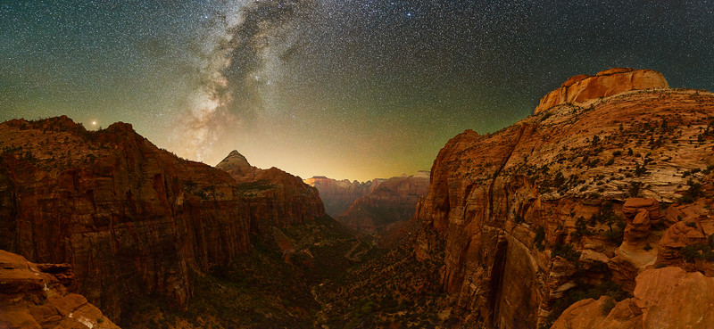 Night With Milkyway and Zion Canyon - Zion NP, Utah<br /> *<br /> Nikon D5, 24mm, f/2.0, 30 sec, ISO 10,000<br /> *<br /> I'm completely surprised this image worked out based on the struggles I had when I first started shooting this night.  This image was taken at the Canyon Overlook from where you can see Zion Canyon.  I had never trekked the 1/2mile little trail until I did in the middle of the night.  I'd never stood at the overlook, the edge of the 500' drop until that night.  Funny enough, I wasn't the only person out there in the middle of the night.  Interestingly enough, I wasn't the only person out there in the middle of the night.  A group was walking around, headlamps glowing, carrying on thinking their sound wasn't echoing throughout the canyon.  Despite all that, setting up and getting to shoot, I immediately realized, I was probably over my head on this.<br /> *<br /> The problem was I was completely unprepared for dealing with the very bright moon and the Milkyway not being positioned well for a good composition.  I had to rethink how I was going to collect the light to make a usable image.  You see the challenge with these situations is everything happens slower because exposures take forever—upwards of 30 seconds.  And, things don't necessarily come together when you combine all that imagery with your computer when you're back at home.  Not only that, shooting so everything was relatively in focus is a super challenge when you're using a large lens aperture to let in as much light as possible.<br /> *<br /> Difficult as it was, this image showed it worked out.<br /> *<br /> This particular image is made from 28 individual image captures taken in two rows of seven positions.  The bottom row had three images shot at each of the seven positions from left to right.  The top row, the sky was only a single image take at the seven positions from left to right.  In post processing, I added another, darker layer, by underexposing the upper layer.  All told, this final image is 35 total files combined into what you see.<br /> *<br /> Why is this important?  It's because night photography is not easy, especially if you're combining images to make a large panorama like I am.  What you see is a very wide composition with an extremely high dynamic range—broad light to dark areas.  It's definitely something that's not viewable with the naked eye.  But, I had a vision, in my mind's eye, of what it should look like.  That's what I created here.<br /> *<br /> I imagined this particular scene when I made my lodging reservations to stay near this stop over a month ago.  But, I had no control over the weather, which turned out fabulous.  Nor did I really estimate where the Milkyway would be when the moon finally set.  I was off by tens of degrees making the Milkyway well off the middle of the canyon when I finally arrived at this point.  Because of the effort—time wasted—making other compositions, by the time I made this composition, I'd been standing at this point for two hours which made the galactic center of the Milkyway move to this very nice position.  In the end everything worked out perfectly.<br /> *<br /> People might be wondering, what's the big deal?  The issue is night photography is a bit like a box of chocolates.  Every time is a little different.  After doing it enough, you become a bit more predictive of what's going to happen during post processing.  Until then, shooting at night is almost a crap shoot, you have no idea what's going to happen.  Turns out, I must've done something right because all 35 image files merged together perfectly to what you see now.  I couldn't be happier.  <br /> *<br /> Sure there are special techniques to make this all workout.  I think the explicit techniques are less important than the overall quality of the imagery.  Making your final image look something similar to your mind's eye is very important, maybe the most important characteristic of these types of images.  <br /> ____________________<br /> *<br /> #Nikon #Nikonphotography #naturephotography #milkyway #night #astrophotography #grandcanyon #arizona #northrim