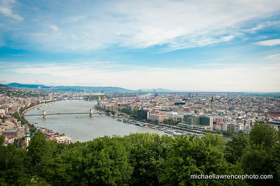 "View of the ""Pest"" side of Budapest, characterized by the flat landscape. The Chain Bridge is in the foreground.  The Chain Bridge was the first permanent stone-bridge connecting Pest and Buda, and only the second permanent crossing on the whole length of the river Danube. It is one of the symbolic buildings of Budapest, the most widely known bridge of the Hungarian capital."