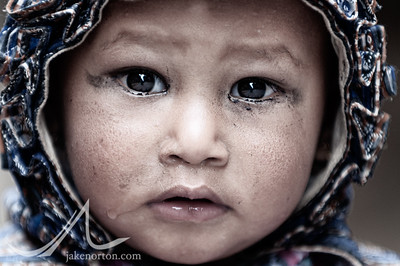 A young girl gazes into the camera in Bhaktapur, Kathmandy Valley, Nepal.
