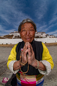 An elderly Tibetan woman prays outside the Potala Palace, Lhasa, Tibet.