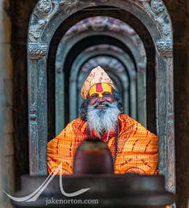A sadhu, or Hindu holy man, poses in front of a four-faced Shiva Lingam at Pashupatinath, Kathmandu, Nepal.