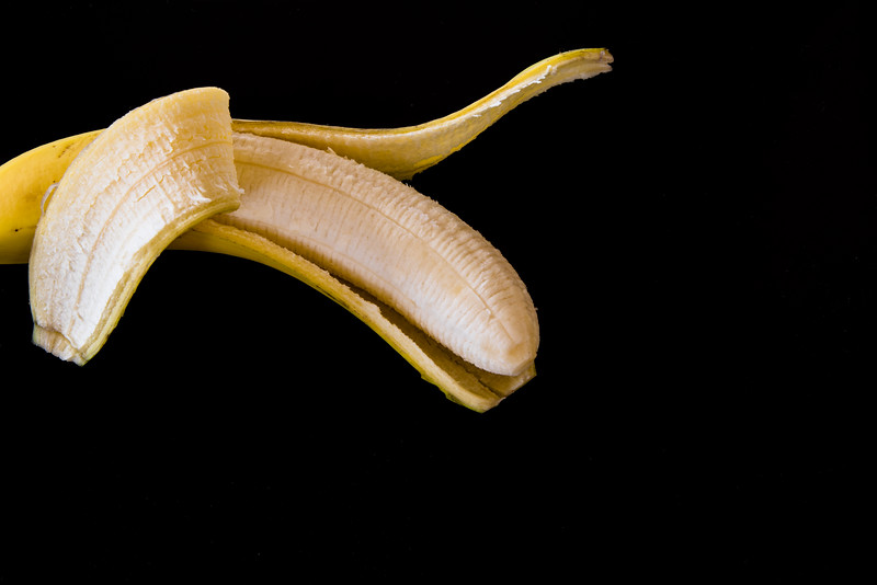 Peeled banana con black background