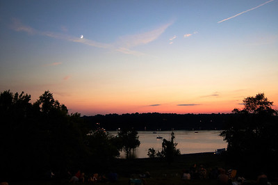 Gorgeous sunset before the fireworks with boats on the lake waiting for the show.