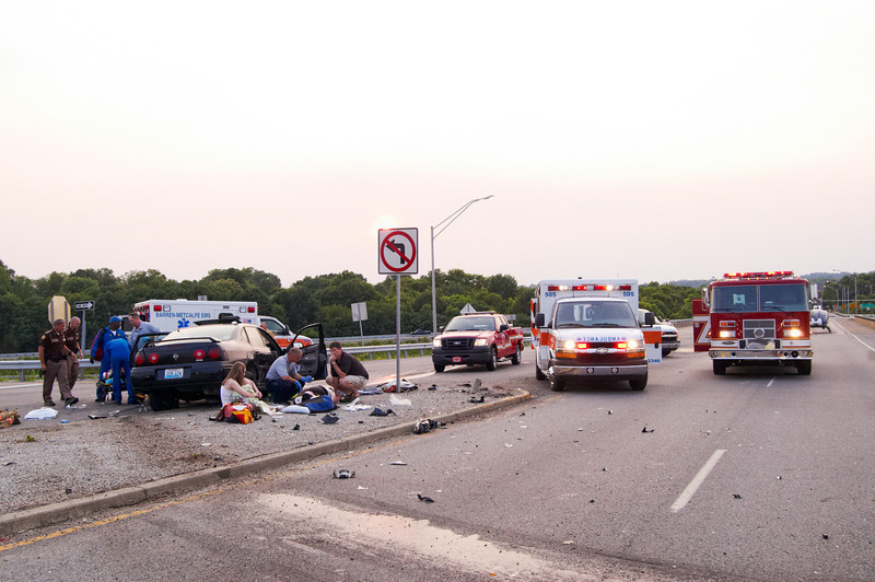 Paramedics can be seen assisting the driver as the multiple rescue vehicles and workers surround the scene.