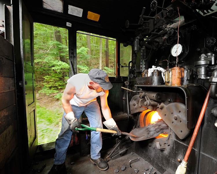 Fireman Chris Lambert shovels coal into the firebox of Big Six on the way to Bald Knob
