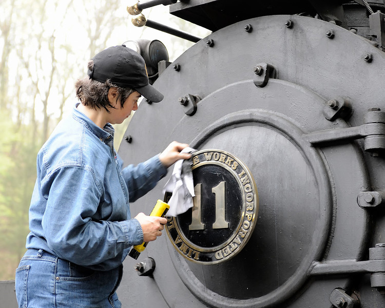 Fireman Amy Beck polishes the brass number plate.  Amy is the first woman to earn the title of Fireman at Cass.