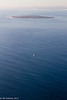 A lone sailing craft on the Atlantic Ocean with Robben Island at the far end.