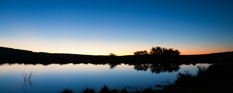 """""""Watering Hole Sunset""""<br /> A panorama taken as the sun sets behind the Cederberg Mountains at a watering hole at Bushmans Kloof Wilderness Reserve."""