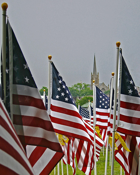 church with American flags and yellow ribbons in foreground honoring troops killed in Iraq