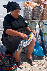 Petticoats are worn by widows traditionally to keep them warm as they waited by the shore for their husbands to return from sea, Promontório do Sítio, Nazaré, Portugal