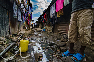 A young boy stands by a trickle of sewage flowing through the streets of Mathare, a slum and home to 500,000 people in Nairobi, Kenya.