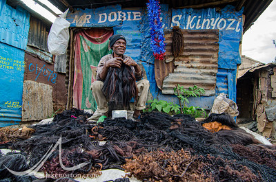 A wig seller sits with his wares in the middle of Mathare, a slum and home to 500,000 people in Nairobi, Kenya.