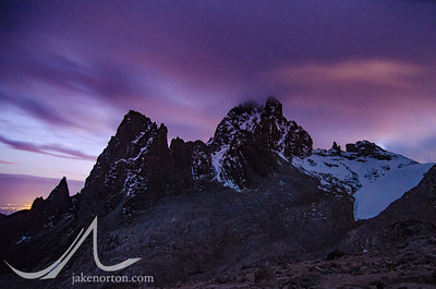 Mt. Kenya's steep walls jut into morning clouds at sunrise with the famed Lewis Glacier sitting to the right; from near Top Hut.