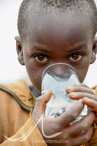 A young girl drinks a glass of safe drinking water outside the Kisaro Community Clinic in Kisaro Sector, Rulindo District, Rwanda.