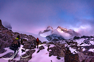 The team picks it's way through rocks and snow to the Stanley Plateau Glacier at sunrise. In the distance, the twin Mount Stanley summits of Alexandra (left) and Margherita (right) rise from the mist.