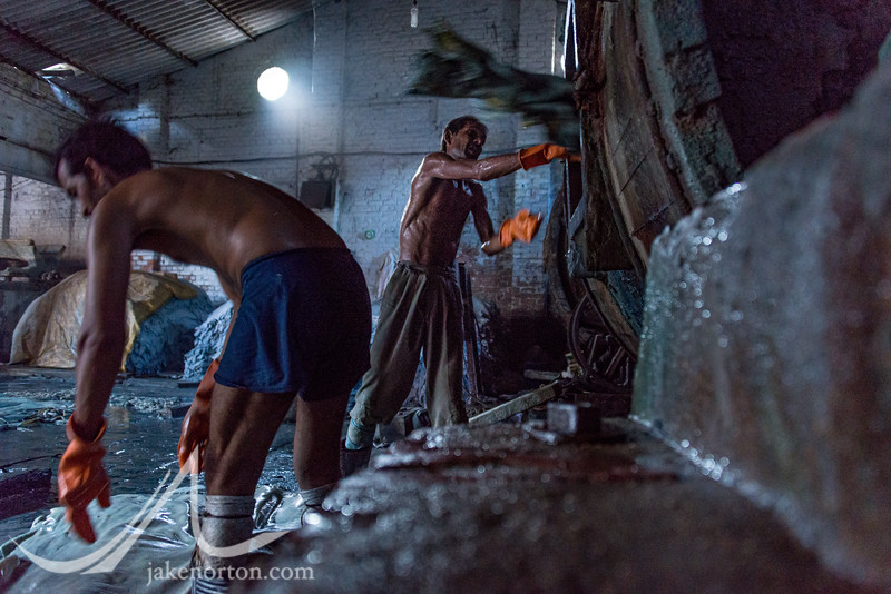 Workers at Sahara Tannery toss lime-soaked hides into vats of chromium and other chemicals.