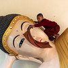 young novice cleaning a reclining buddha