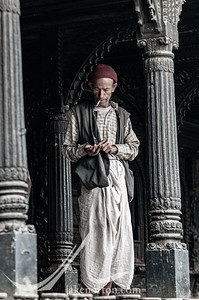 A Nepali man dressed in traditional clothing smoking a cigarette at a temple in Bhaktapur, Nepal.