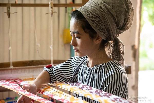 woman working on a weaving loom