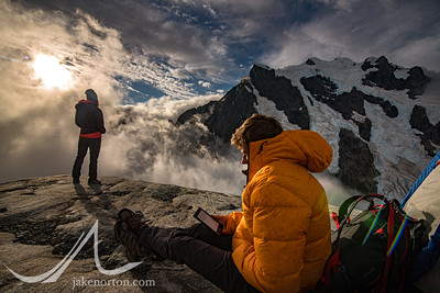 Lynsey Dyer and Cory Richards enjoy some downtime at Turner's Bivvy on Mount Medline, New Zealand, with Mount Tutoko rising behind.