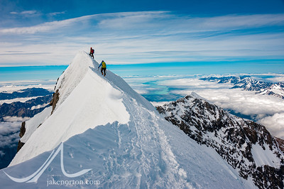 David Morton belays Charley Mace up to the steep summit of Aoraki (Mount Cook), New Zealand.