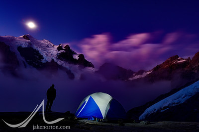 A lone tent perched at Turner's Bivvy on the slopes of Mount Madeline, New Zealand. In the distance, a full moon rises over Mount Tutoko, the highest peak in the Darran Mountains.