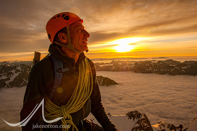 Charley Mace enjoys the first rays of sunlight from high on Aoraki (Mount Cook), New Zealand.
