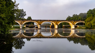 Old train bridge across the Dordogne River, France.
