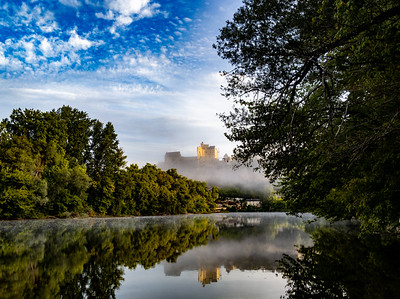 Château de Beynac rises in the mist above the Dordogne River, France.